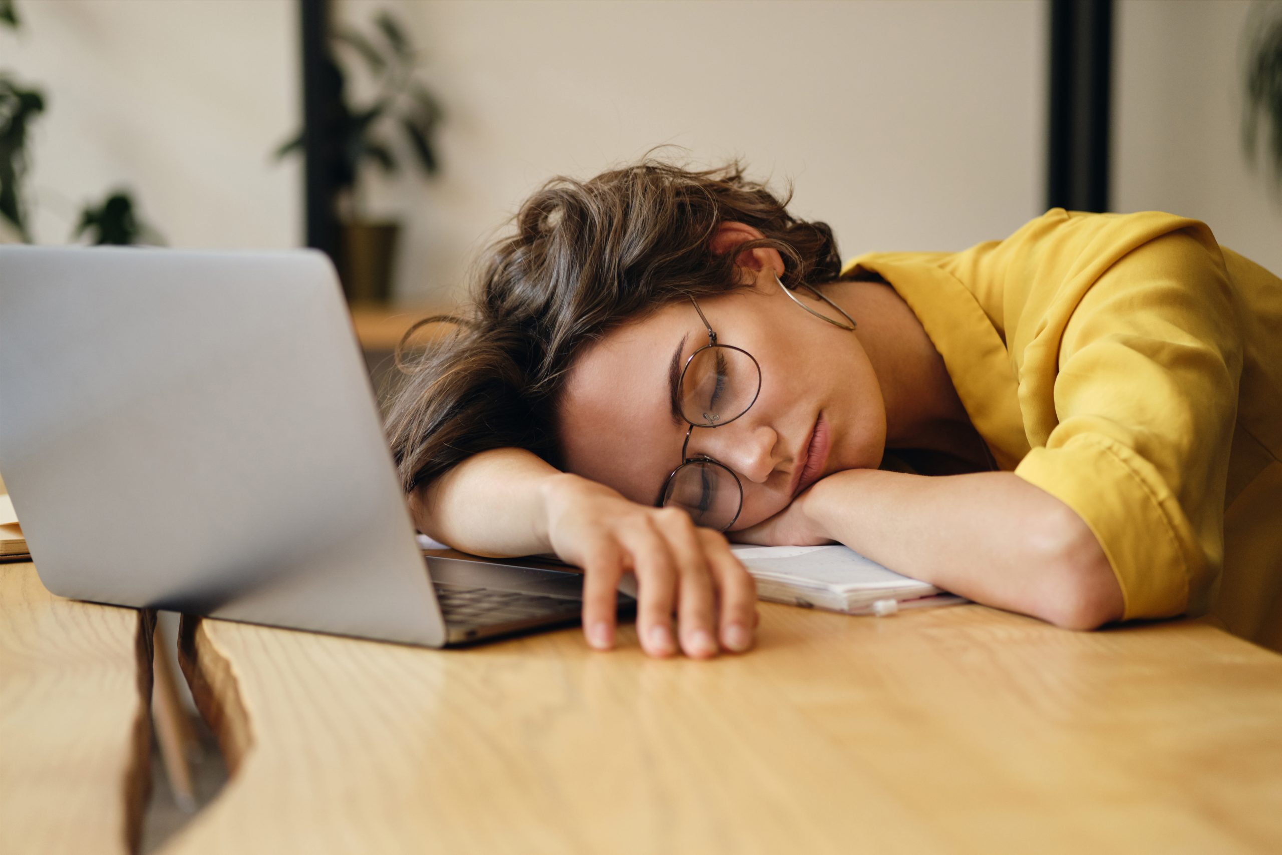 Young Tired Woman In Eyeglasses Sleeping On Desk With Laptop At Workplace Alone