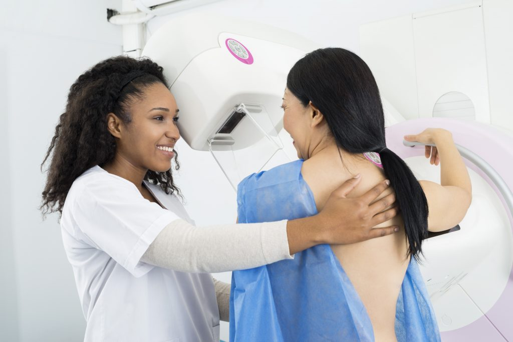 Happy Doctor Assisting Woman Undergoing Mammogram